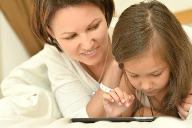 Gelukkig moeder en dochtertje met tablet pc in bed