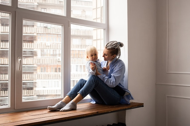 Gelukkig moeder en jongenskind zittend op raam in quarantaine