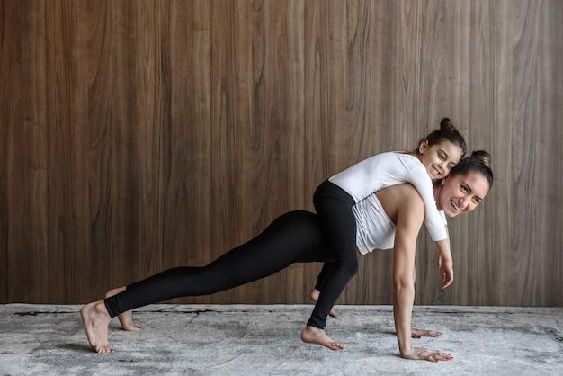 Gelukkig moeder en kind meisje trainen samen yoga in de hal op de vloer op het tapijt