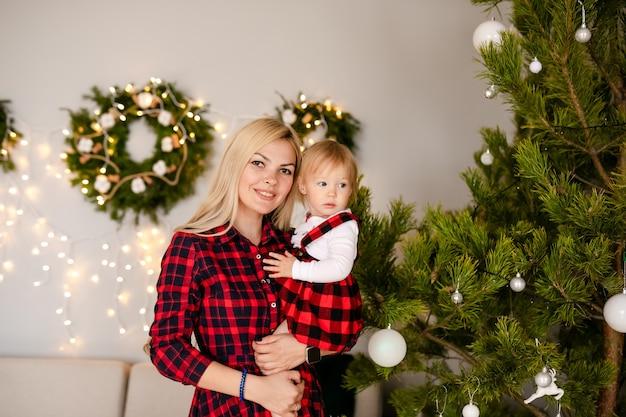 Gelukkig moeder en kindmeisje dichtbij een kerstboom