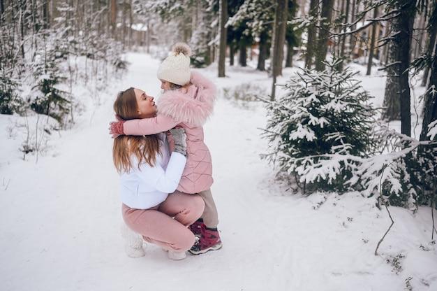 Gelukkig moeder en klein schattig meisje in roze warme uitloper wandelen met plezier en knuffelen in besneeuwde witte koude winter naaldbos met sparren bossen buitenshuis