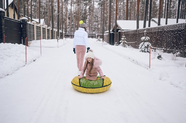 Gelukkig moeder en klein schattig meisje in roze warme uitloper wandelen plezier rijdt opblaasbare sneeuw buis in besneeuwde witte koude winter forest buitenshuis