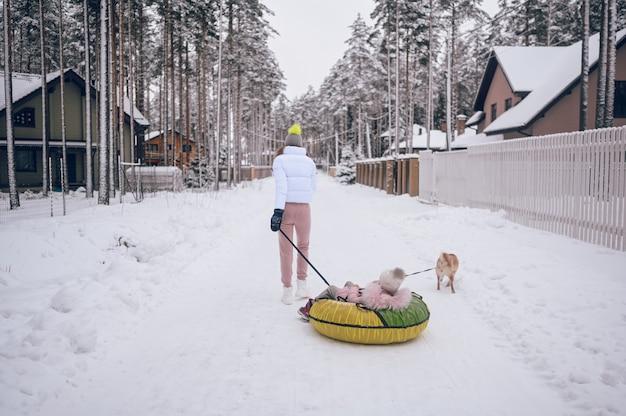 Gelukkig moeder en klein schattig meisje in roze warme uitloper wandelen plezier rijdt opblaasbare sneeuw buis met rode shiba inu hond in besneeuwde witte winter platteland buitenshuis