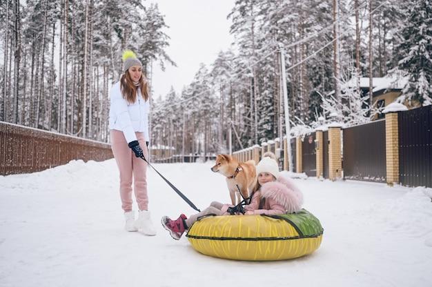 Gelukkig moeder en klein schattig meisje in roze warme uitloper wandelen plezier rijdt opblaasbare sneeuwbuis