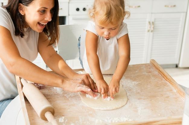 Gelukkig moeder en meisje die koekjes voorbereiden