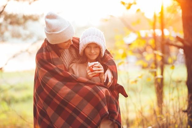 Gelukkig moeder en meisje met mok op herfstdag gewikkeld in een deken