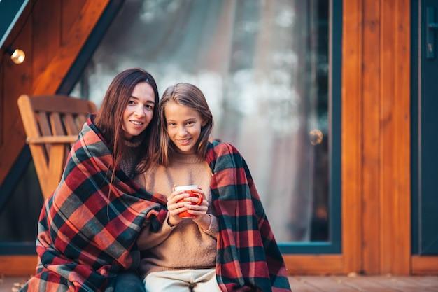 Gelukkig moeder en meisje met mok op herfstdag verpakt in een deken buitenshuis