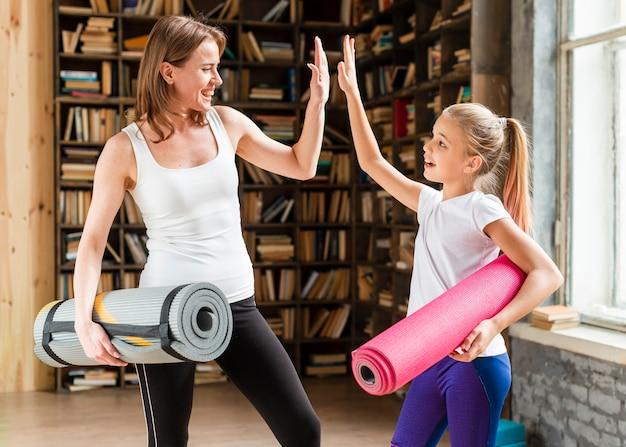 Gelukkig moeder en meisje met yogamatten en high fiving