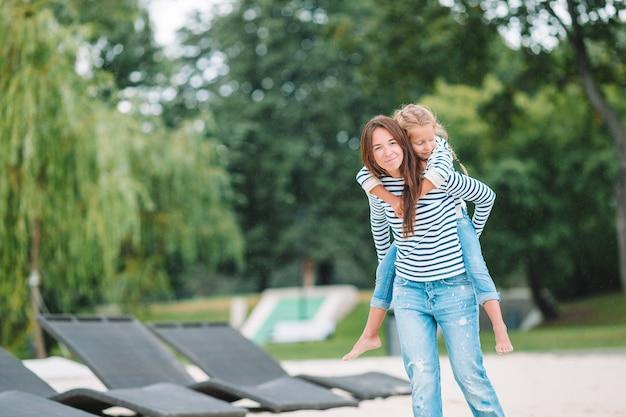 Gelukkig moeder en schattig klein meisje genieten van zomervakantie