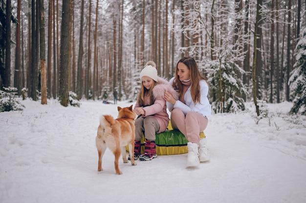 Gelukkig moeder en schattig meisje in roze warme uitloper wandelen plezier rijdt opblaasbare sneeuw buis met rode shiba inu hond in besneeuwde witte koude winter forest buitenshuis