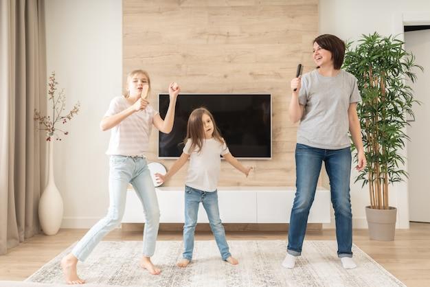 Gelukkig moeder en twee dochters plezier zingen karaoke lied in haarborstels.