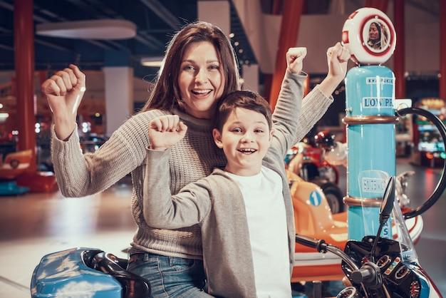 Gelukkig moeder en zoon op speelgoed motorfiets in winkelcentrum