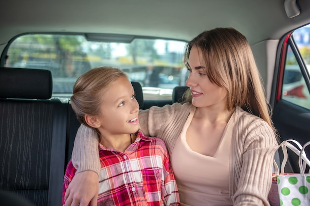 Gelukkig moeder haar dochter knuffelen op de achterbank van de auto