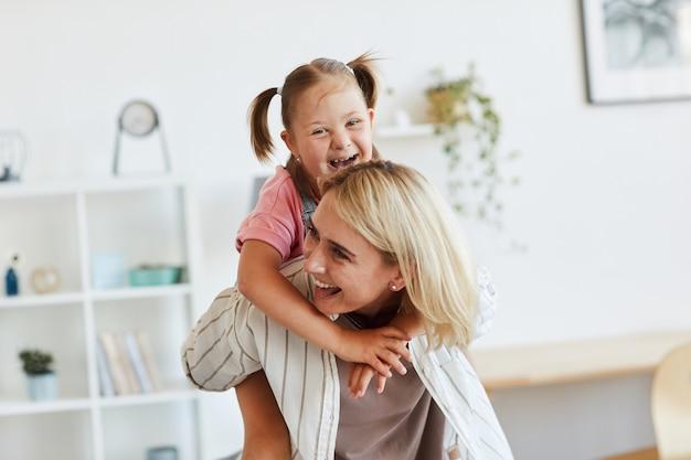 Gelukkig moeder haar dochtertje rijden op haar rug ze plezier thuis