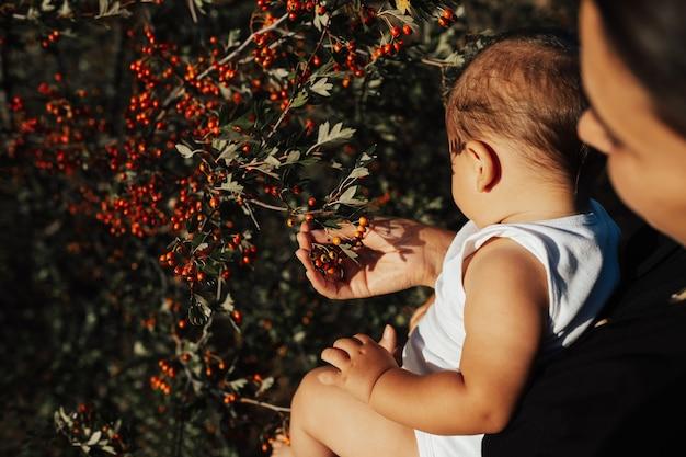 Gelukkig moeder hand in hand een babyjongen gekleed in het witte t-shirt staande in het park in de achtergronden van groene struik met rode rozenbottel