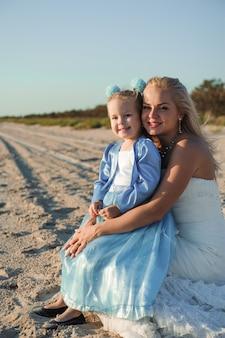 Gelukkig moeder in de trouwjurk met haar dochter op het strand.