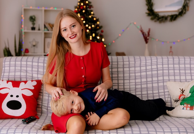 Gelukkig moeder in rode jurk met haar kleine kind die op haar knieën op een bank ligt met plezier samen tv kijken in een ingerichte kamer met kerstboom op de achtergrond