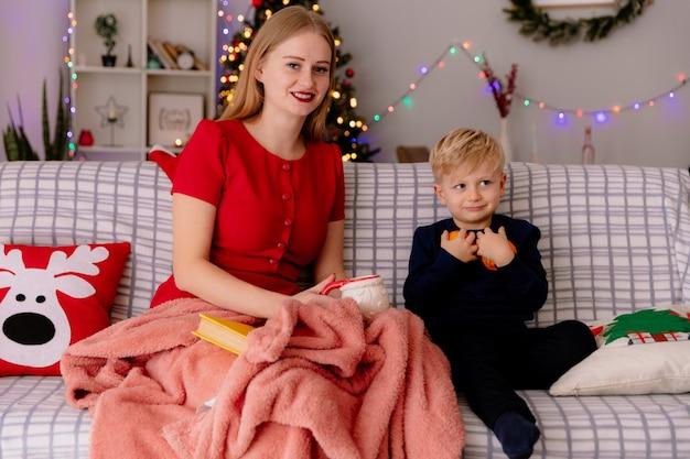 Gelukkig moeder in rode jurk met kopje thee en haar kleine kind sinaasappelen houden onder deken in een ingerichte kamer met kerstboom op de achtergrond