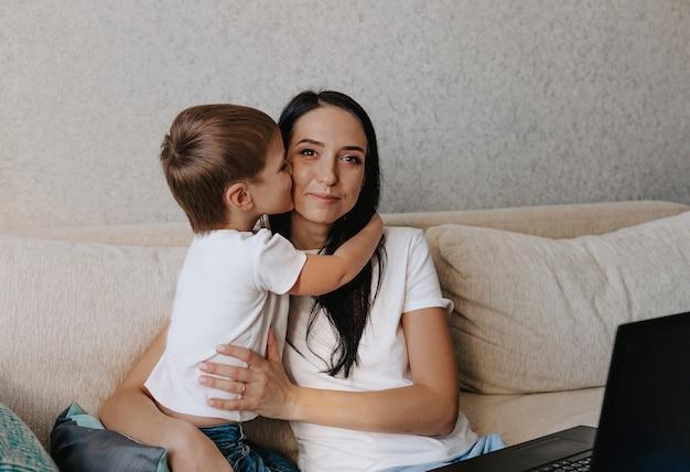 Gelukkig moeder knuffelt haar jonge zoon zittend op de bank voor haar laptop