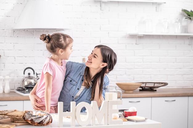 Gelukkig moeder met dochter bereiden zelfgemaakte taarten op de achtergrond van een lichte keuken.