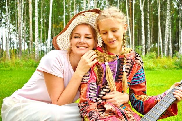 Gelukkig moeder met een dochter in de zomer op de natuur