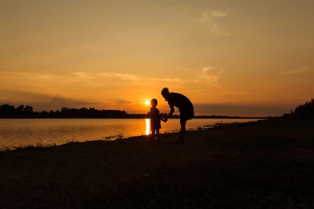 Gelukkig moeder met haar zoon spelen en kijken naar de zonsondergang