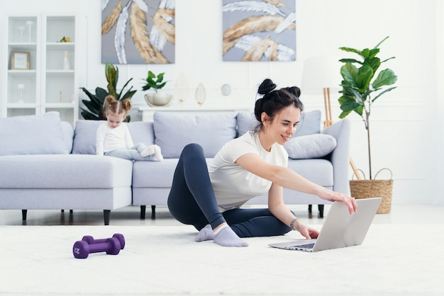 Gelukkig moeder op de vloer thuis met laptop