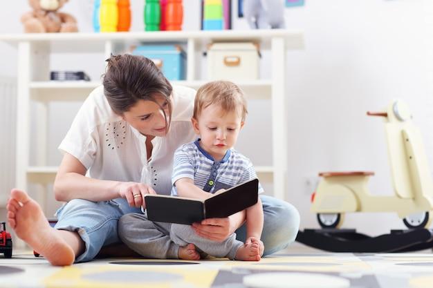 Gelukkig moeder spelen met babyjongen thuis