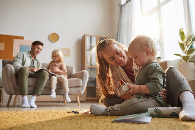 Gelukkig moeder spelen met haar baby op de vloer en vader spelen met oudere zoon in de kamer
