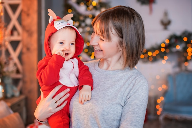 Gelukkig moeder spelen met haar peuter in rood santa rendier kostuum op kerstboom achtergrond