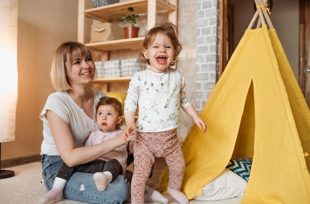 Gelukkig moeder spelen op de vloer met twee tweelingmeisjes. gele hut