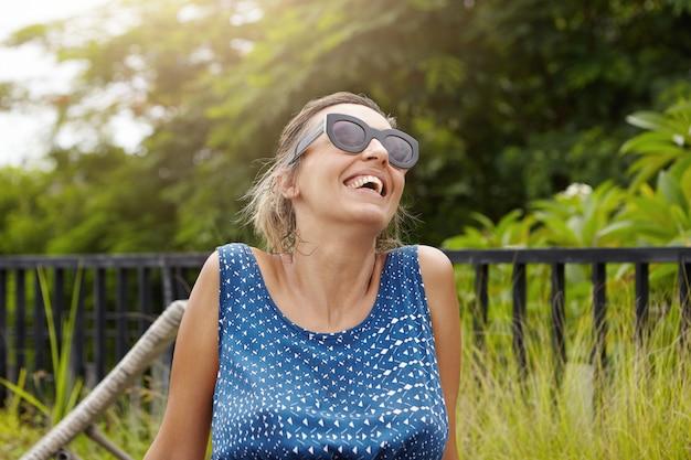 Gelukkig moederschap concept. headshot van mooie zwangere vrouw in tinten leuke tijd buiten doorbrengen, frisse lucht inademen en lachen, haar hoofd achterover gooien op groene bomen