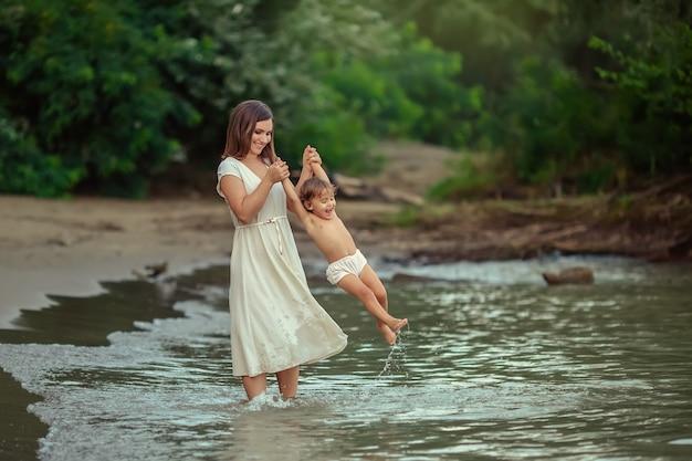 Gelukkig moederschap. een jonge moeder speelt in de zomer met haar anderhalf jaar oude dochter op de oever van de rivier. ze hebben plezier met spetteren in het water