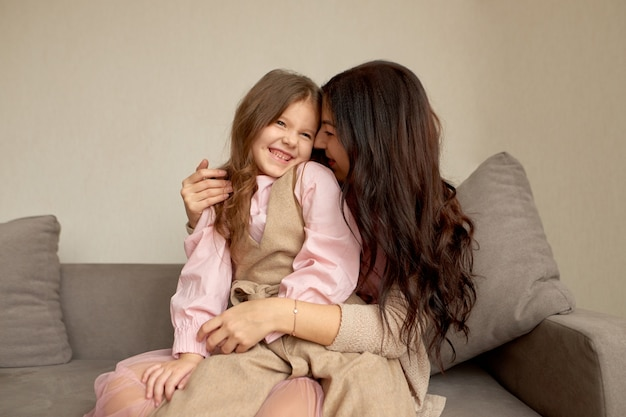 Gelukkig moederschap, koesteren, familieband en onvoorwaardelijk liefdesconcept. liefdevolle moeder zittend op de bank neuzen gezicht met schattige dochtertje aan te raken