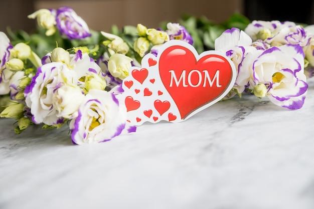 Gelukkig moedersdagconcept eustoma bloeit boeket met rood hart op oud marmeren bureau. kopieer ruimte