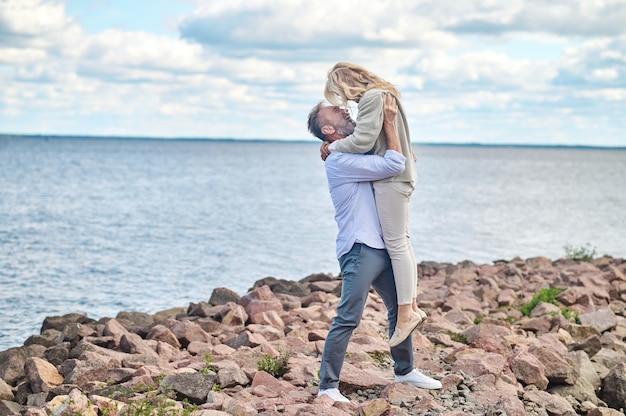 Gelukkig moment. enthousiaste volwassen bebaarde man die op mooie dag in zijn armen een vrolijke blonde vrouw aan de kust opheft