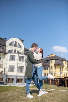 Gelukkig moment. jonge volwassen man en vrouw in truien en spijkerbroeken die buiten knuffelen tegen de achtergrond van nieuwe huizen new