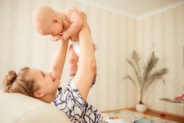 Gelukkig moment van jongensbaby en zijn moeder. mooie moeder stijgt het kind in de slaapkamer. kinderen lachen vrolijk. moeder en kind relatie concept