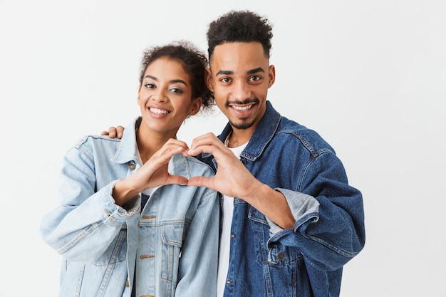 Gelukkig mooi afrikaans paar in denimoverhemden die hartteken over grijze muur tonen
