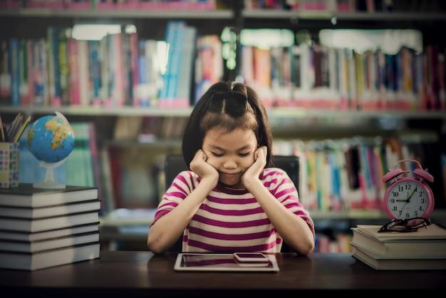 Gelukkig mooi aziatisch meisje dat mobiele telefoon bekijkt