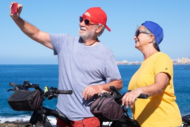 Gelukkig mooi bejaarde echtpaar dat op de klif staat en een selfie maakt met smartphone. actieve gepensioneerden genieten van een gezonde levensstijl met fietsen - horizon over water