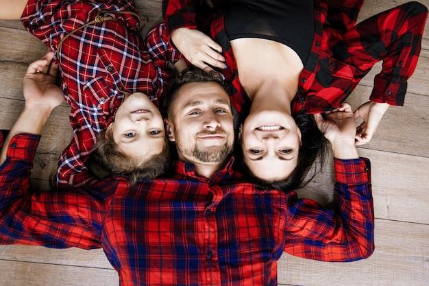 Gelukkig mooi en gelukkig gezin samen thuis liggend op het bovenaanzicht van de houten vloer