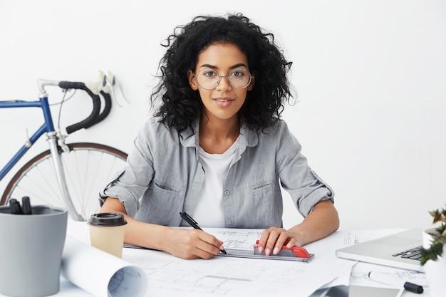 Gelukkig mooi gemengd ras vrouw ingenieur tekeningen of schetsen maken met liniaal