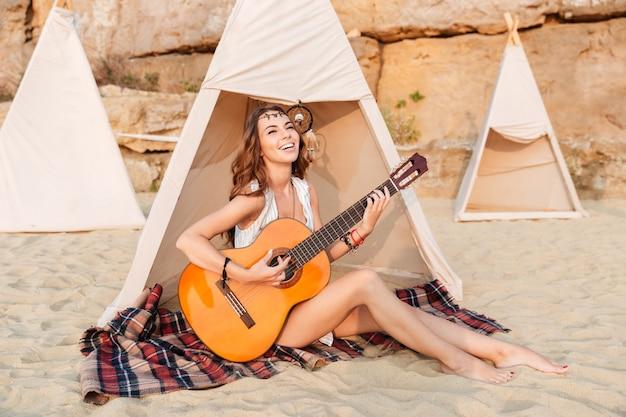Gelukkig mooi hippiemeisje dat gitaar speelt terwijl ze in de tent op het strand zit