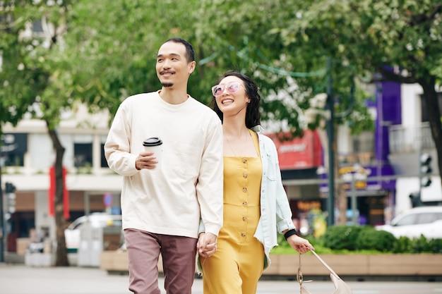 Gelukkig mooi jong chinees stel hand in hand wanneer ze door de straten van de stad lopen