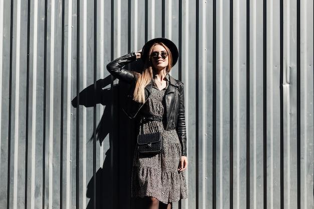 Gelukkig mooi jong hipster meisje in trendy kleding met zonnebril en hoed in mode jurk en leren jas met stijlvolle handtas in de buurt van metalen wand