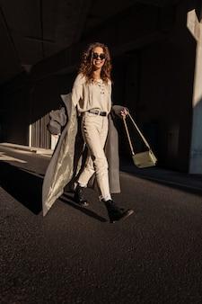 Gelukkig mooi jong meisje in een modieuze lange jas met een tas wandelingen in de stad. krullend grappig meisje met een glimlach op straat