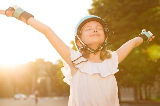 Gelukkig mooi jong meisje met beschermende kleding en helm voor skaten en in de zomer buiten frisse lucht inademen