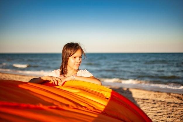 Gelukkig mooi jong meisje met donker haar staat in de buurt van een lichte tent glimlachend op het zandstrand van de blauwe glanzende zee