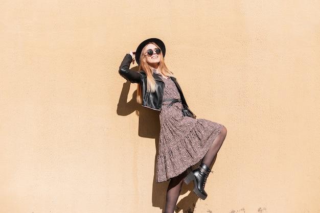 Gelukkig mooi jong meisje met een glimlach in modieuze outfit look met een vintage jurk, leren jas, hoed en zonnebril in de buurt van een beige textuur muur in de straat